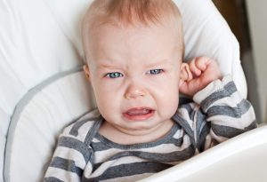 Baby crying holding his ear