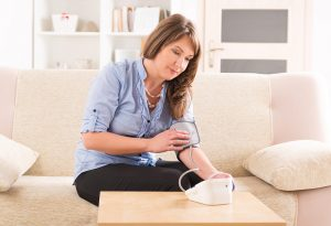 Woman measuring blood pressure at home after delivery