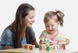 mother teaches letters using blocks