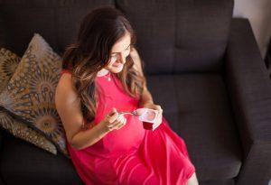 pregnant woman eating yoghurt