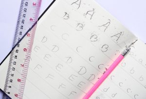 the child practice handwriting alphabet with pencil