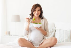 Pregnant woman eating greens