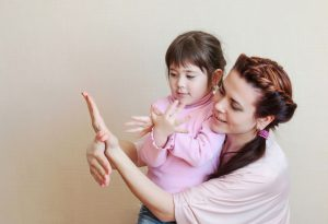 Mother teaching girl to sign 'bird'
