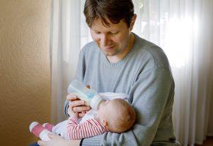 Dad feeding formula milk to baby