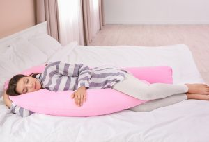 Pregnant woman sleeping on maternity pillow