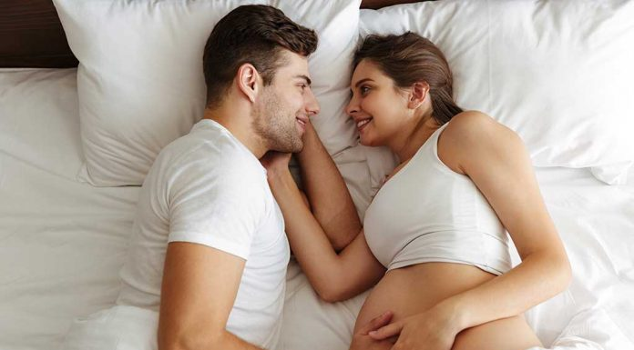 A pregnant wife and husband on bed