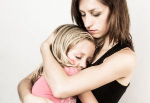 Mother hugging daughter