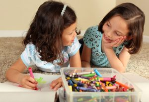Sisters playing with crayons