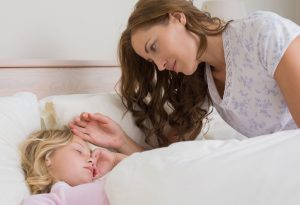 Mother looking over sleeping child