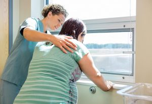 Pregnant woman being helped by nurse