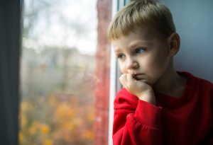 A little boy sitting by the window looking worried