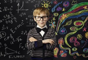 A child with spectacles standing against a blackboard full of art and mathematical formulas