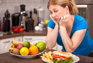 Woman with healthy and junk food