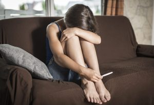 A young woman sitting on the couch, unhappy with her positive pregnancy result