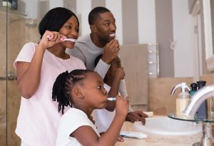 Parents teach child to brush teeth