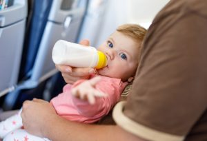 Baby in aeroplane with feeding bottle