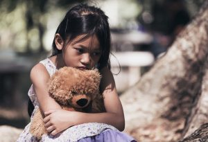 A little girl sitting with her teddy bear, feeling depressed