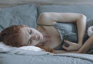 A depressed young woman lying in bed