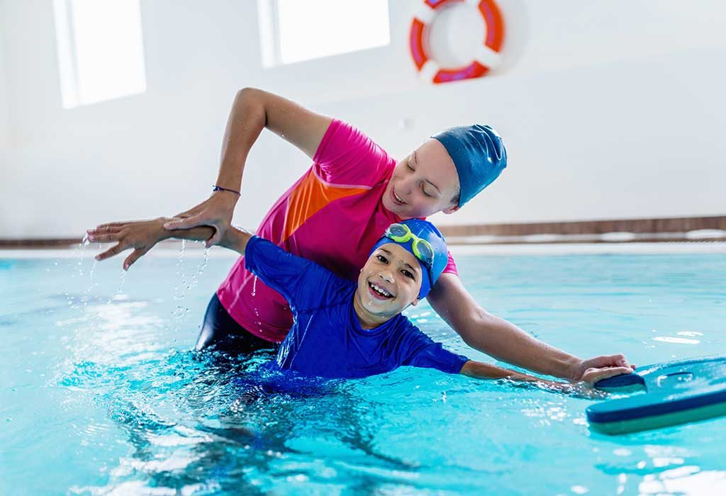 An instructor teaching swimming to a boy