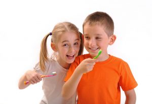 A little girl and  a boy brushing their teeth