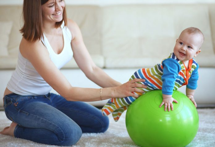 A mother and baby playing with a gymnastic ball