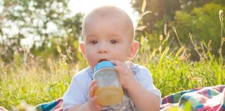 A baby drinking juice