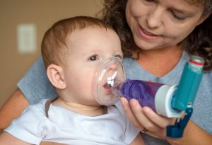 Mother givingbreathing treatment to her baby