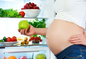 A pregnant woman picking a fruit from the refrigerator
