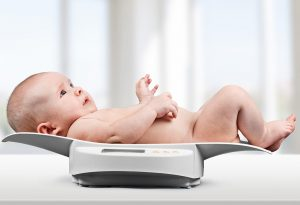 A baby on a weighing scale at the doctor's clinic