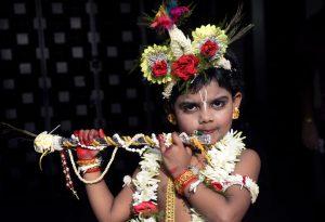A little boy dressed as Lord Krishna