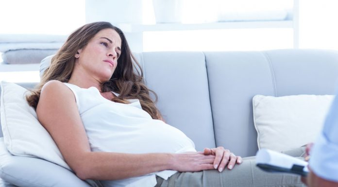 Pregnant woman resting on the couch in a daze