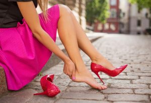 A woman in red heels experiencing pain in her feet
