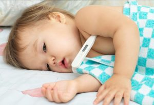 Baby with an electric thermometer, suffering from a fever