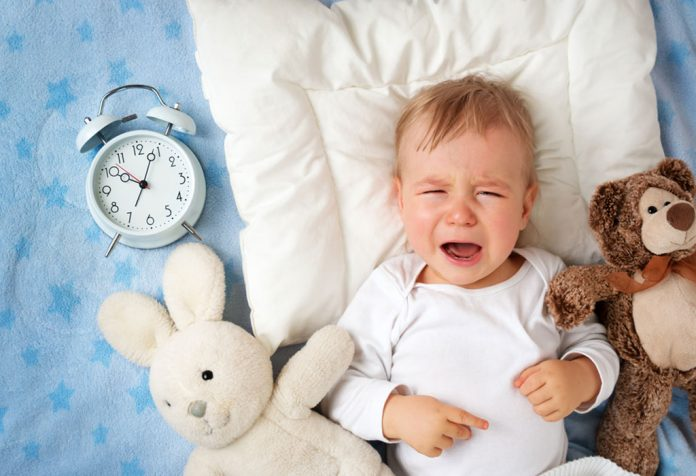 A baby crying at night with an alarm clock and teddy by his side