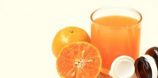 Vitamin C tablets and and an orange