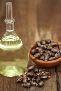 Castor oil with beans on a wooden surface