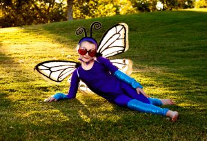 A little girl wearing a butterfly costume