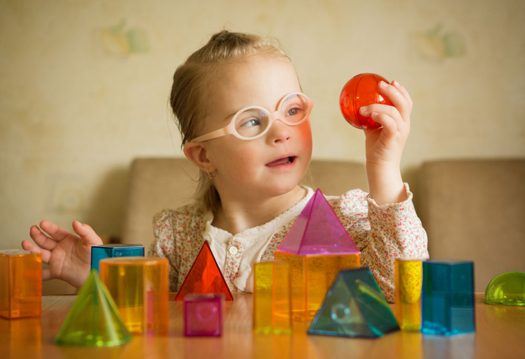A little girl with Down syndrome playing with geometrical shapes