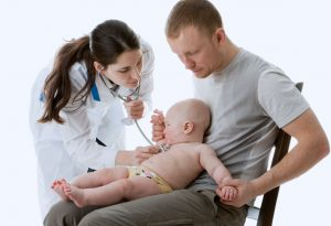 A doctor checking an infant sitting on the father's lap