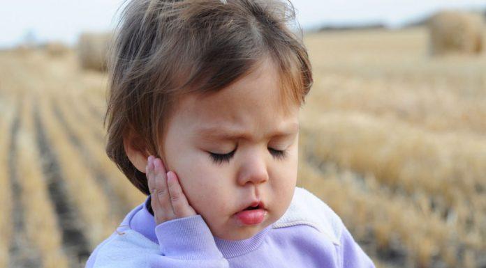 girl holding her ear