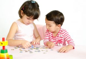 Two children solving puzzle