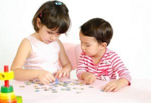 Two children solving puzzle