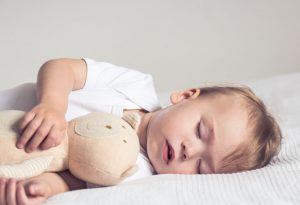 Baby sleeping with a toy
