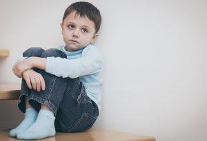 A sad child sitting alone