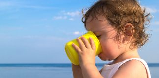 A child drinking water from a yellow mug