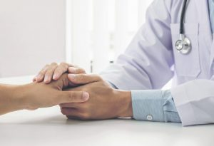 A doctor holding a patient's hand for encouragement