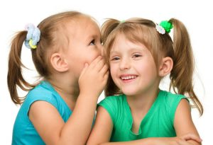 One girl whispering in other girl's ears