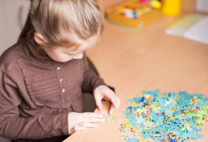 girl playing with jigsaw puzzle
