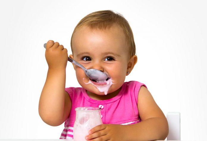 A baby girl eating yogurt