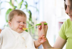 A baby crying when given food